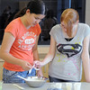 Camille Green, 13, left, and Michelle Bridenstine, 14, mix ingredients during the teen cooking session of making Mediterranean dishes with at the Mamie Doud Eisenhower Public Library on Tuesday.<br /> <br /> July 5 2011<br /> staff photo/ David R. Jennings