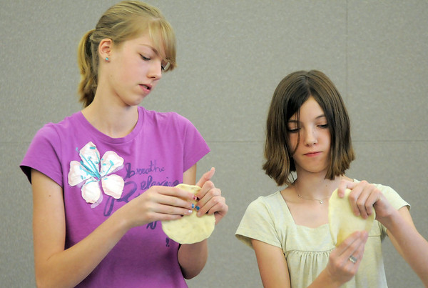 Sisters Sharon Hendrix, 14, left, and Michelle, 12,  shape dough while learning how to make Mediterranean dishes with chef Luke Zauke with the Knife and Cork at the Mamie Doud Eisenhower Public Library on Tuesday.<br /> <br /> July 5 2011<br /> staff photo/ David R. Jennings