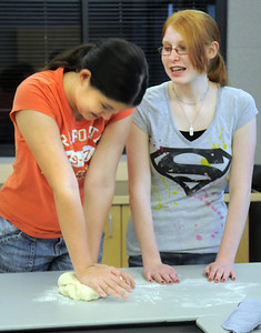 Camille Green, 13, left, kneads bread dough while Emily Bridenstine, 14, watches during the teen cooking session of making Mediterranean dishes with at the Mamie Doud Eisenhower Public Library on Tuesday.  July 5 2011 staff photo/ David R. Jennings