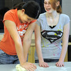 Camille Green, 13, left, kneads bread dough while Emily Bridenstine, 14, watches during the teen cooking session of making Mediterranean dishes with at the Mamie Doud Eisenhower Public Library on Tuesday.<br /> <br /> July 5 2011<br /> staff photo/ David R. Jennings