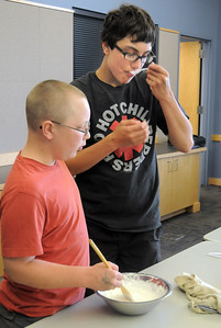 Paris Sitchler, 13, right, takes a taste of the dish he and his brother Val, 12, made during the teen cooking session of making Mediterranean dishes with at the Mamie Doud Eisenhower Public Library on Tuesday.   July 5 2011 staff photo/ David R. Jennings