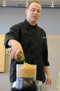 Knife and Cork chef Luke Zautke demonstrates how to make hummus to the class during the teen cooking session of making Mediterranean dishes with at the Mamie Doud Eisenhower Public Library on Tuesday.   July 5 2011 staff photo/ David R. Jennings