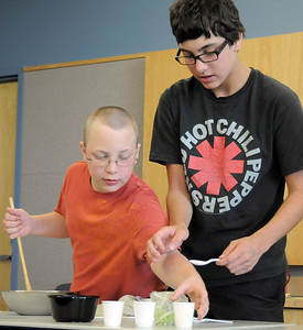 Val Sitchler, 12, left, and his brother Paris, 13, mix ingredients during the teen cooking session of making Mediterranean dishes with at the Mamie Doud Eisenhower Public Library on Tuesday.   July 5 2011 staff photo/ David R. Jennings