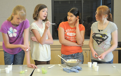 Camille Green, 13, center right, and Emily Bridenstine, 14,far right,  have Sharon Hendrix, 14, left, and her sister Michelle, 12, taste their dish during the teen cooking session of learning how to make Mediterranean dishes with chef Luke Zauke with the Knife and Cork at the Mamie Doud Eisenhower Public Library on Tuesday.  July 5 2011 staff photo/ David R. Jennings
