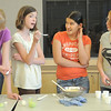 Camille Green, 13, center right, and Emily Bridenstine, 14,far right,  have Sharon Hendrix, 14, left, and her sister Michelle, 12, taste their dish during the teen cooking session of learning how to make Mediterranean dishes with chef Luke Zauke with the Knife and Cork at the Mamie Doud Eisenhower Public Library on Tuesday.<br /> <br /> July 5 2011<br /> staff photo/ David R. Jennings