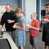 Chef Luke Zauke, left,  prepares to to cook flattened bread while  Layla Clark 13, Val Sitchler, 12, and his brother Paris, 13, wait in line during the teen cooking session of making Mediterranean dishes with at the Mamie Doud Eisenhower Public Library on Tuesday.<br /> <br /> July 5 2011<br /> staff photo/ David R. Jennings
