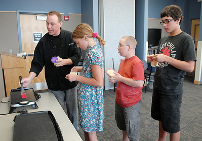 Chef Luke Zauke, left,  prepares to to cook flattened bread while  Layla Clark 13, Val Sitchler, 12, and his brother Paris, 13, wait in line during the teen cooking session of making Mediterranean dishes with at the Mamie Doud Eisenhower Public Library on Tuesday.  July 5 2011 staff photo/ David R. Jennings