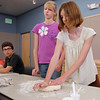 Michelle Hendrix, 12, right, kneads dough while her sister, Sharon, 14, waits her turn during the teen cooikn session of learning how to make Mediterranean dishes with chef Luke Zauke with the Knife and Cork at the Mamie Doud Eisenhower Public Library on Tuesday.<br /> July 5 2011<br /> staff photo/ David R. Jennings