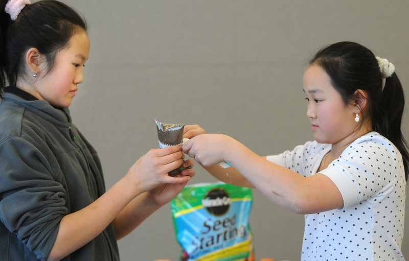 Holly Vuong, 12, left,  helps her sister Anna, 11, tie a ribbon on a little pot for a plant during the Holiday Crafts for Teens program at Mamie Doud Eisenhower Public Library on Saturday.<br /> December 5, 2009<br /> Staff photo/David R. Jennings