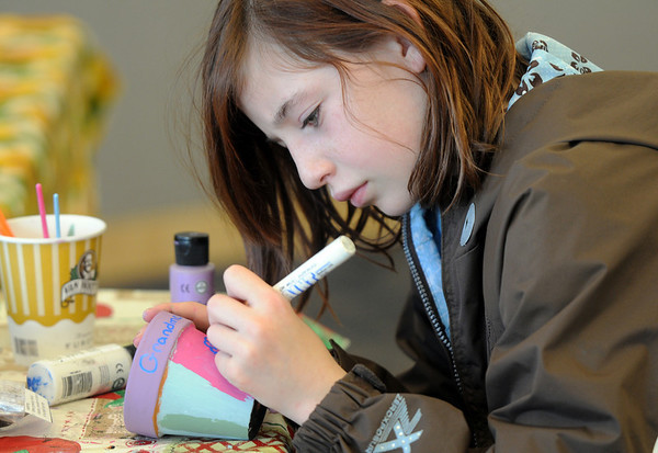 Alison White, 11, decortates a small pot for a plant during the Holiday Crafts for Teens program at Mamie Doud Eisenhower Public Library on Saturday.<br /> December 5, 2009<br /> Staff photo/David R. Jennings