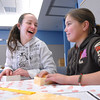 Michaela Peters, 13, left, laughs with Bailey Estes, 12, while making oragami boxes at the Holiday Crafts for Teens program at Mamie Doud Eisenhower Public Library on Saturday.<br /> December 5, 2009<br /> Staff photo/David R. Jennings