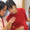 Triplette sisters Monica Mah, 11, left, and Nicole put their heads together to figure out how to make a wool beaded necklace during the Holiday Crafts for Teens program at Mamie Doud Eisenhower Public Library on Saturday.<br /> December 5, 2009<br /> Staff photo/David R. Jennings