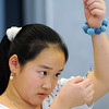 Anna Vuong, 11, studies the beaded necklace she's making while wearing a wool beaded braclet during the Holiday Crafts for Teens program at Mamie Doud Eisenhower Public Library on Saturday.<br /> December 5, 2009<br /> Staff photo/David R. Jennings