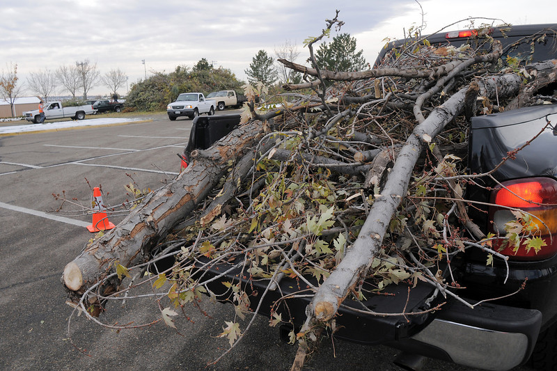 Trucks full of broken branches wait to unload at the temporary tree branch drop off in the parking lot of the Bay Aquatic Center on Saturday.<br /> October 29, 2011<br /> staff photo/ David R. Jennings