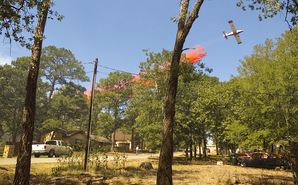 Texas Wildfires.JPEG-02471.JPG A plane drops fire retardant on a house on Mauna Kea Lane in the Tahitian Village neighborhood in Bastrop, Texas,  on Monday Sept. 5, 2011. A house on the street was burned to the ground. A roaring wildfire raced unchecked Monday through rain-starved farm and ranchland in Texas, destroying nearly 500 homes during a rapid advance fanned in part by howling winds from the remnants of Tropical Storm Lee. (AP Photo/Austin American-Statesman, Jay Janner)  MAGS OUT; NO SALES; TV OUT; INTERNET OUT EXCEPT FOR AP MEMBERS