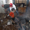 Texas Wildfires.JPEG-05b7d.JPG Home owner, Dennis Kleiber, left, uses a chainsaw to cut a hole in his floor to get to smoldering wood as Brian Schultz uses a bucket of water to put out ambers from the fire on Cedar Lane in the Blue Bonnet Acres subdivision west of Bastrop, Texas on Monday, Sept. 5, 2011.  A roaring wildfire raced unchecked Monday through rain-starved farm and ranchland in Texas, destroying nearly 500 homes during a rapid advance fanned in part by howling winds from the remnants of Tropical Storm Lee. (AP Photo/Austin American-Statesman, Rodolfo Gonzalez)  MAGS OUT; NO SALES; TV OUT; INTERNET OUT EXCEPT AP MEMBERS)