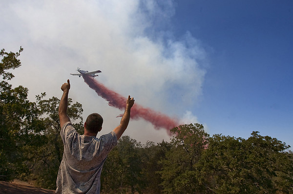 Texas Wildfires.JPEG-04e51.JPG Brian Covish, waves to fire bombers from the roof of his home on Cedar Lane in the Blue Bonnet Acres subdivision west of Bastrop, Texas on Monday, Sept. 5, 2011.  A roaring wildfire raced unchecked Monday through rain-starved farm and ranchland in Texas, destroying nearly 500 homes during a rapid advance fanned in part by howling winds from the remnants of Tropical Storm Lee. (AP Photo/Austin American-Statesman, Rodolfo Gonzalez)  MAGS OUT; NO SALES; TV OUT; INTERNET OUT EXCEPT AP MEMBERS)