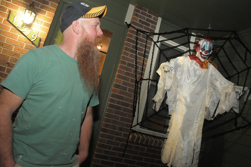 Peter Anderson explains the scary clown character  in the family's Halloween display on Maria Circle in Brandywine on Thursday. <br /> October 20, 2011<br /> staff photo/ David R. Jennings