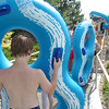 Children carry tubes to the top of the big blue water slide at The Bay Aquatic Center.