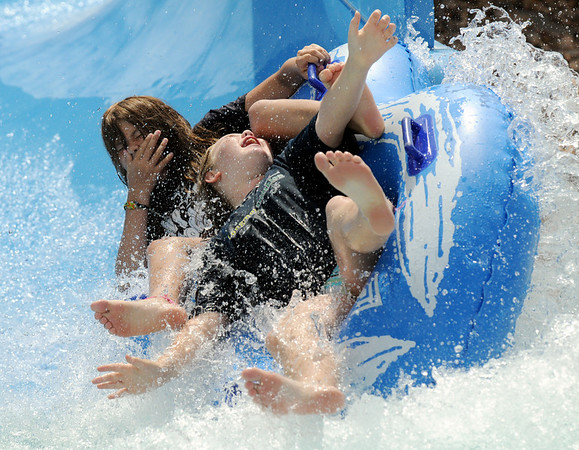 Carissa Bratcher, 10, front, and Rebecca King, 11, take a spill at the finish of the blue slide while playing at The Bay Aquatic Center.
