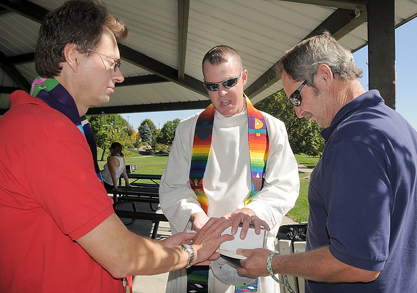 Pastors Thomas Cross, left, and Scott McAnally say a blessing with Craig Chiess over the ashes of  his dog Sugar during the blessing of the animals at Community Park on Saturday.<br /> October 1, 2011<br /> staff photo/ David R. Jennings