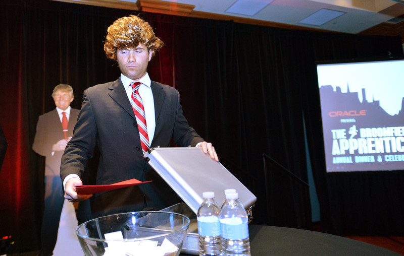 Chamber board chair Tom Orlando, wearing a wig, reveal the winner of the Broomfield Apprentice program during the Broomfield Chamber of Commerce's annual dinner at the Renaissance Hotel on Thursday.<br /> January 31, 2013<br /> staff photo/ David R. Jennings