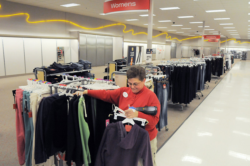 Janet Stephenson a Target employee for 2 1/2 years puts items on a sales rack on the last day of the Broomfield Target store, Saturday.  Items not sold will be sent to other Target stores.<br /> January 26, 2012<br /> staff photo/ David R. Jennings