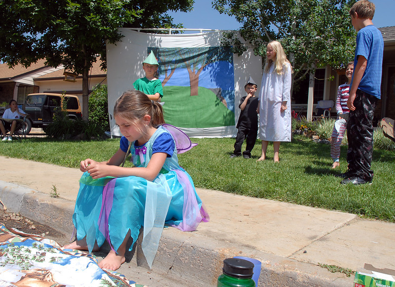 Tinkerbell, Maycee Bricker, 7, left, sits on the curb during Saturday's dress rehearsal of the Lemonade Players neighborhood production of Peter Pan .<br /> <br /> June 25, 2011<br /> staff photo/ David R. Jennings