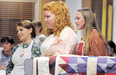 Corrie Ellington, left, Molly Crouse and Madison Wagnaar   stand behind quilts while waiting to go on stage during rehearsal for the Aster Women's Choir presentation of the Quilters. September 20, 2011 staff photo/ David R. Jennings