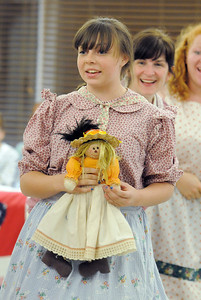 Sarah Kochevar, playing the young Sarah, sings while holding a doll during rehearsal for the Aster Women's Choir presentation of the Quilters. September 20, 2011 staff photo/ David R. Jennings