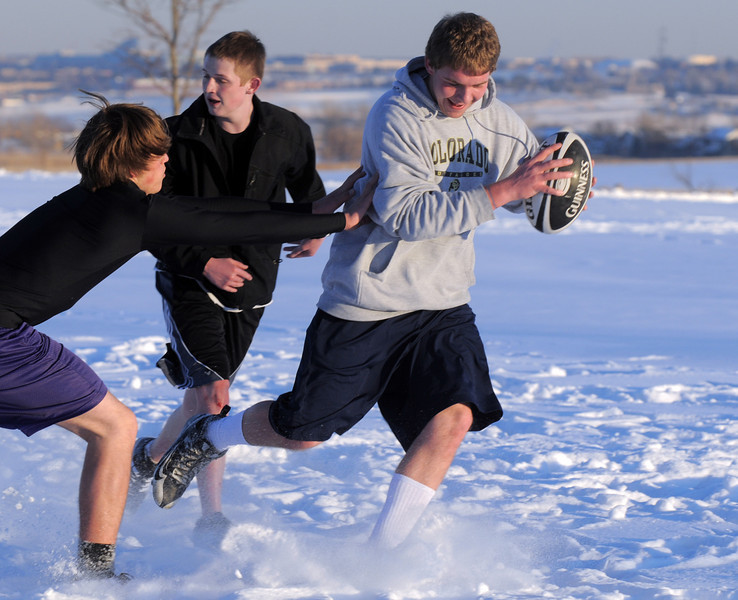 Andrew Hutchinson avoids a tackle by Matt Wright  during Tigers Rugby practice on the Championship Field at the Broomfield County Commons Park on Thursday.<br /> February 9, 2011<br /> staff photo/David R. Jennings