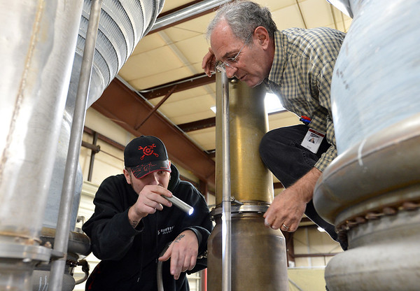 Redstone College student Benjamin Nelson, left, and instructor Steve Hankle look at and discuss what parts maybe needed for restoration of a Titan I rocket engine for display at the Wings Over the Rockies Air and Space Museumat the school on Tuesday.<br /> February 19, 2013<br /> staff photo/ David R. Jennings