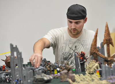 Mike Lewis moves a gaming piece while playing Warhammer 40k  at Total Escape Games on Thursday. The gaming store is holding a ThanksGaming Day fundraiser for Broomfield FISH. October 25, 2012 staff photo/ David R. Jennings