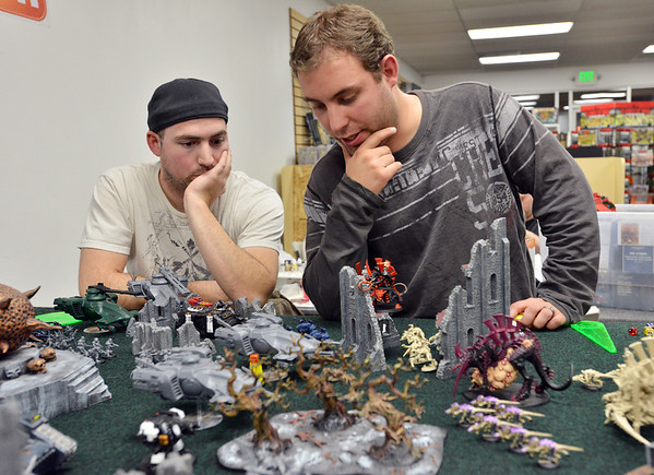 Mike Lewis, left, watches while Bobby Bradshaw prepare for his next move as they play Warhammer 40k at Total Escape Games on Thursday. The gaming store is holding a ThanksGaming Day fundraiser for Broomfield FISH.<br /> October 25, 2012<br /> staff photo/ David R. Jennings
