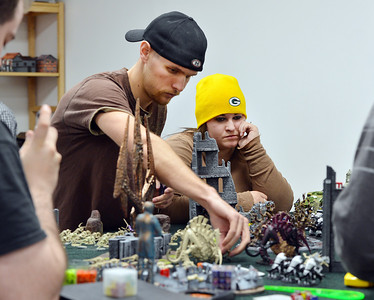 Devin Dewhurst, left, moves game pieces as Amanda Bradshaw studies the move while playing Warhammer 40k at Total Escape Games on Thursday. The gaming store is holding a ThanksGaming Day fundraiser for Broomfield FISH. October 25, 2012 staff photo/ David R. Jennings