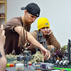 Devin Dewhurst, left, moves game pieces as Amanda Bradshaw studies the move while playing Warhammer 40k at Total Escape Games on Thursday. The gaming store is holding a ThanksGaming Day fundraiser for Broomfield FISH.<br /> October 25, 2012<br /> staff photo/ David R. Jennings