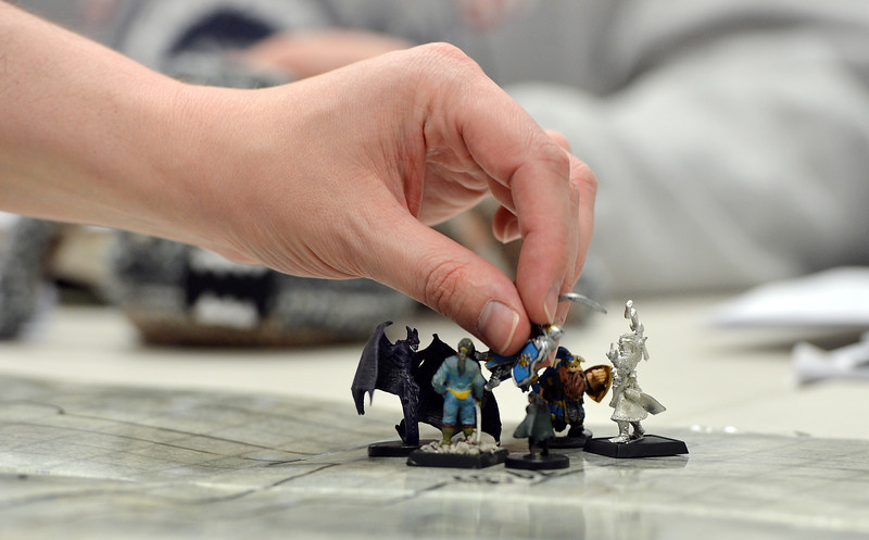 Andy Schiller, left, moves his game piece while playing the role playing game Pathfinder at Total Escape Games on Thursday. The gaming store is holding a ThanksGaming Day fundraiser for Broomfield FISH.<br /> October 25, 2012<br /> staff photo/ David R. Jennings