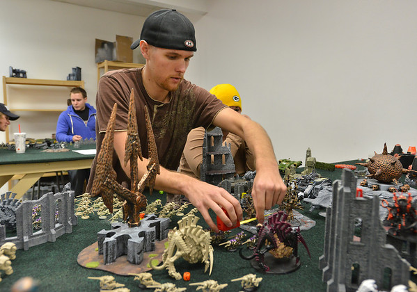 Devin Dewhurst carefully measures the distance his characters can move on the board while playing Warhammer 40k at Total Escape Games on Thursday. The gaming store is holding a ThanksGaming Day fundraiser for Broomfield FISH.<br /> October 25, 2012<br /> staff photo/ David R. Jennings
