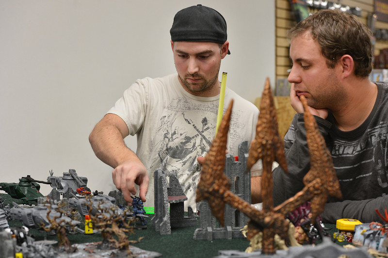 Mike Lewis, left, makes a move with Bobby Bradshaw watching as they play Warhammer 40k at Total Escape Games on Thursday. The gaming store is holding a ThanksGaming Day fundraiser for Broomfield FISH.<br /> October 25, 2012<br /> staff photo/ David R. Jennings
