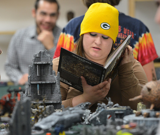 Amanda Bradshaw studies the Warhammer 40k book while determining her next move at Total Escape Games on Thursday. The gaming store is holding a ThanksGaming Day fundraiser for Broomfield FISH.<br /> October 25, 2012<br /> staff photo/ David R. Jennings