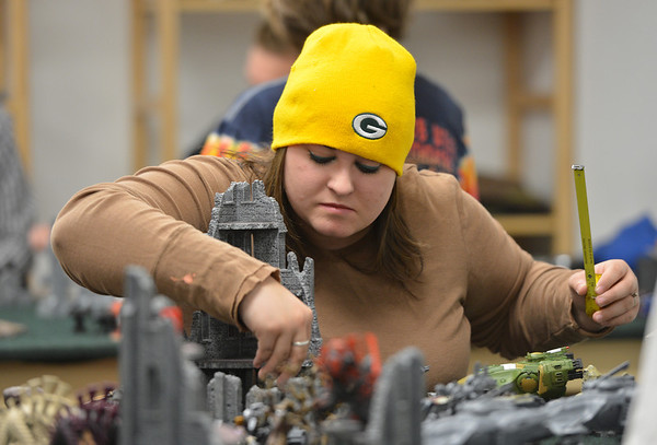Amanda Bradshaw, with a tape measure in hand, moves gaming pieces while playing Warhammer 40k  at Total Escape Games on Thursday. The gaming store is holding a ThanksGaming Day fundraiser for Broomfield FISH.<br /> October 25, 2012<br /> staff photo/ David R. Jennings