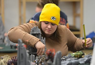 Amanda Bradshaw, with a tape measure in hand, moves gaming pieces while playing Warhammer 40k  at Total Escape Games on Thursday. The gaming store is holding a ThanksGaming Day fundraiser for Broomfield FISH. October 25, 2012 staff photo/ David R. Jennings