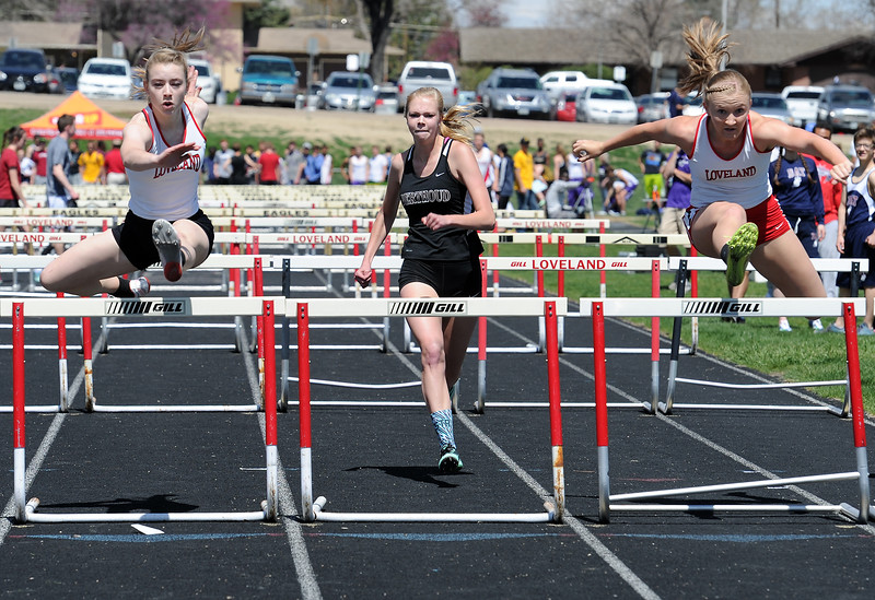 Loveland's Hannah Weinmaster, left, and Alex Koschel, right, and Berthoud's Alyssa Strong, center, run the girls 100 meter hurdles Thursday, April 14, 2016, during a track meet at Loveland High School. (Photo by Jenny Sparks/Loveland Reporter-Herald)