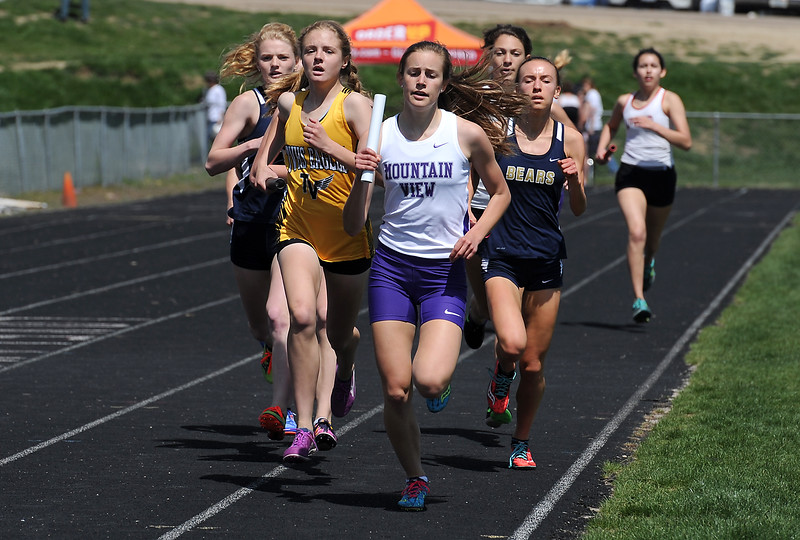 Thompson Valley's Emily Black, left, and Mountain View's McKenna Delinger, right, run the girls 4X800 meter relay Thursday, April 14, 2016, during a track meet at Loveland High School. (Photo by Jenny Sparks/Loveland Reporter-Herald)