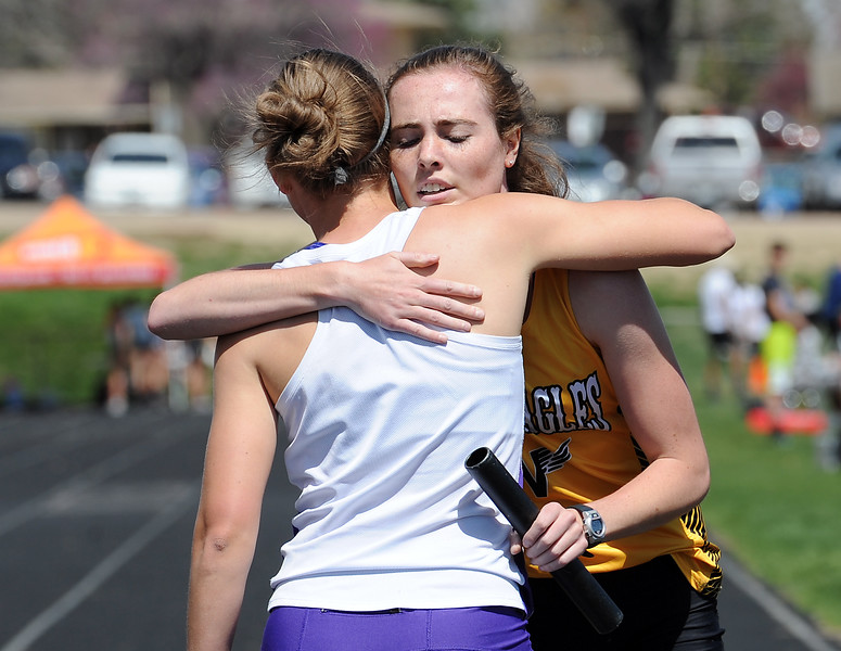 Thompson Valley's Emily Leidig, right, and Mountain View's Lauren Offerman hug after running the girls 4X800 meter relay Thursday, April 14, 2016, during a track meet at Loveland High School. (Photo by Jenny Sparks/Loveland Reporter-Herald)