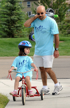 Nate Garner carries a plastic trike as his daughter Elizabeth, 4, rides her tricycle while walking the trail during the Broomfield Trail Adventure and Children's Wellness day at Anthem Highlands Parkside Community Center on Saturday.<br /> June 5, 2010<br /> Staff photo/ David R. Jennings