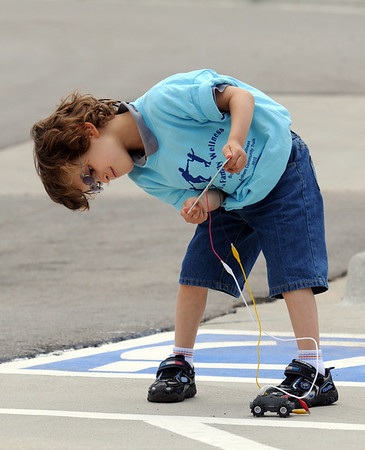 Samuel Cardona, 5,  holds a photovoltaic panel to power an electric toy car during the Broomfield Trail Adventure and Children's Wellness day at Anthem Highlands Parkside Community Center on Saturday.<br /> June 5, 2010<br /> Staff photo/ David R. Jennings