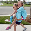 Madi Brown 8 1/2, carries her friend Tanna Tennyson, 9, while watching walkers  finish during the Broomfield Trail Adventure and Children's Wellness day at Anthem Highlands Parkside Community Center on Saturday.<br /> June 5, 2010<br /> Staff photo/ David R. Jennings