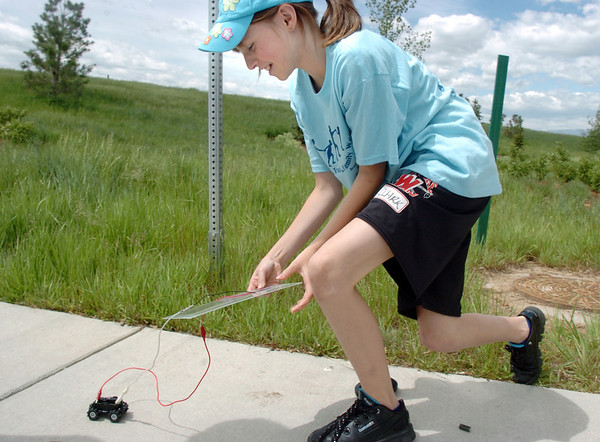 Layla Clark, 11, left, chases after a toy car posered by a photovoltaic panel during the solar power workshop at the Broomfield Trail Adventure and Children's Wellness day at Anthem Highlands Parkside Community Center on Saturday.<br /> June 5, 2010<br /> Staff photo/ David R. Jennings