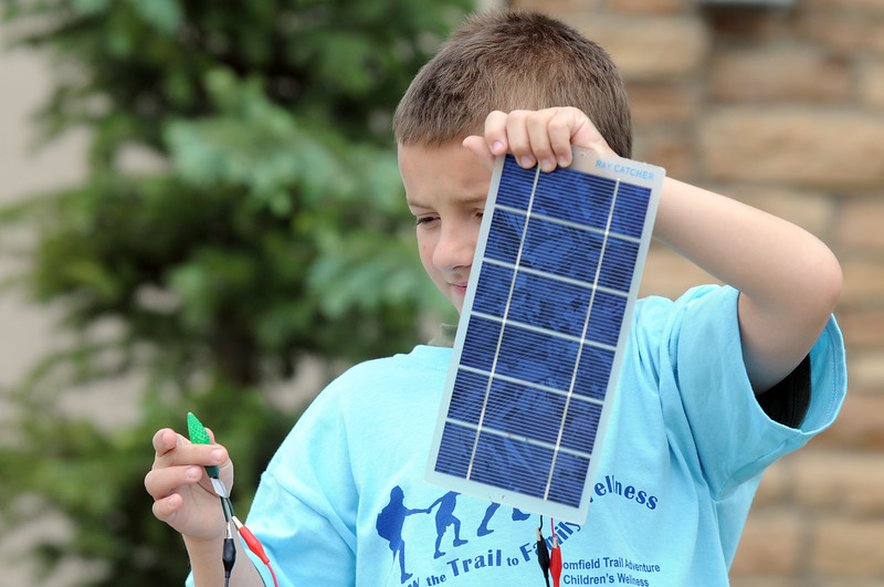 Maxim Tuell, 8, holds a photvoltaic panel to light a LED lamp during the solar power workshop at Broomfield Trail Adventure and Children's Wellness day at Anthem Highlands Parkside Community Center on Saturday.<br /> June 5, 2010<br /> Staff photo/ David R. Jennings